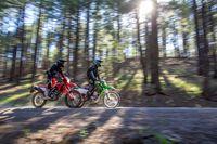 Honda CRF300L 2021 e Kawasaki KLX300 2021 na estrada com árvores no pano de fundo.